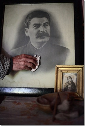 Zhiuli Sikmashvili of the Communism Party of Georgia sweeps the dust off the Stalin's portrait in the Stalin's museum in Tbilisi