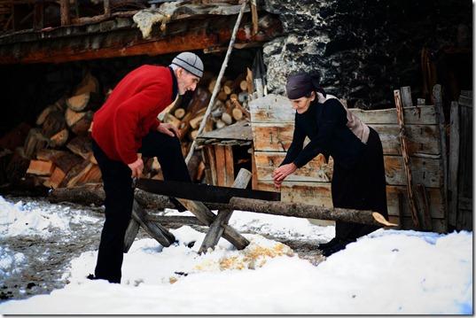 Natalia Qaldani helps her husband saw firewood