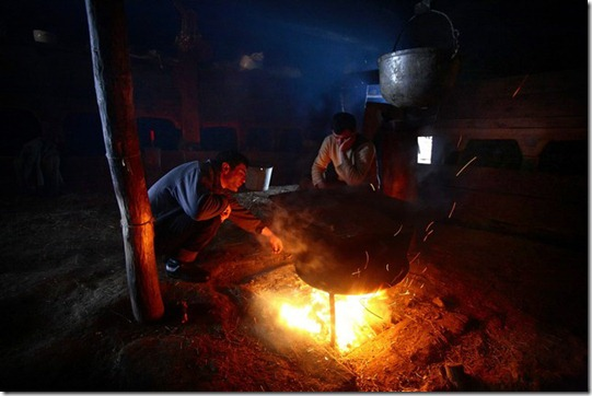 Adishi villagers boil water in a big pan to prepare pig-meat for the holiday feast