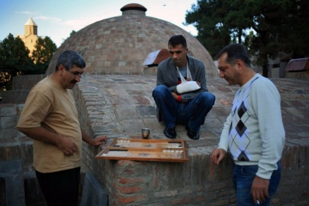 The residents of Tbilisi's oldest district Abanotubani (Bath District) playbackgammon next to the dome of one of the baths. October 12, 2012