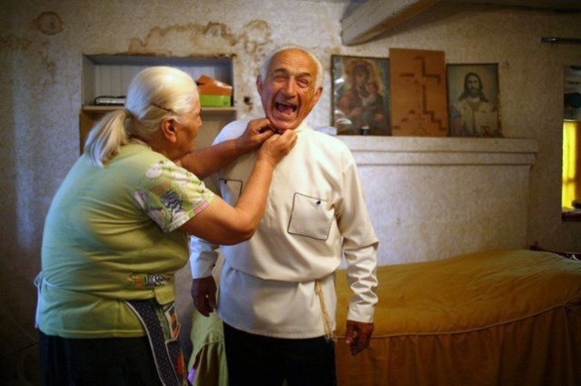 Veteran folk singer Iuza Beradze makes a joke, as his wife helps him fasten the traditional Imeretian dress. Beradze, who lost his son during the war in Abkhazia in 1990s, says that only the song and humor helped him survive all these years.