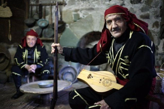 Zaqro Parselidze, a veteran folk musician, poses with a traditional Machakhela rifle and a panduri, a string instrument popular in many Georgian regions.