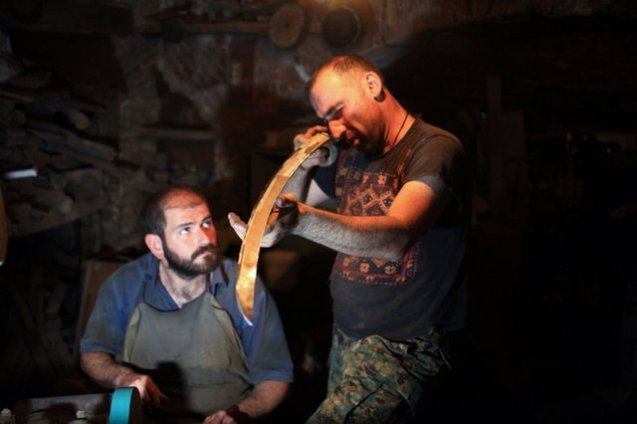 lacksmith Giga Gorgiashvili (left) watches his friend and companion Zakro Nonikashvili evaluate the sharpness of a sword blade. For almost a decade now Gorgiashvili has been a man behind the armory of The Black Shields.